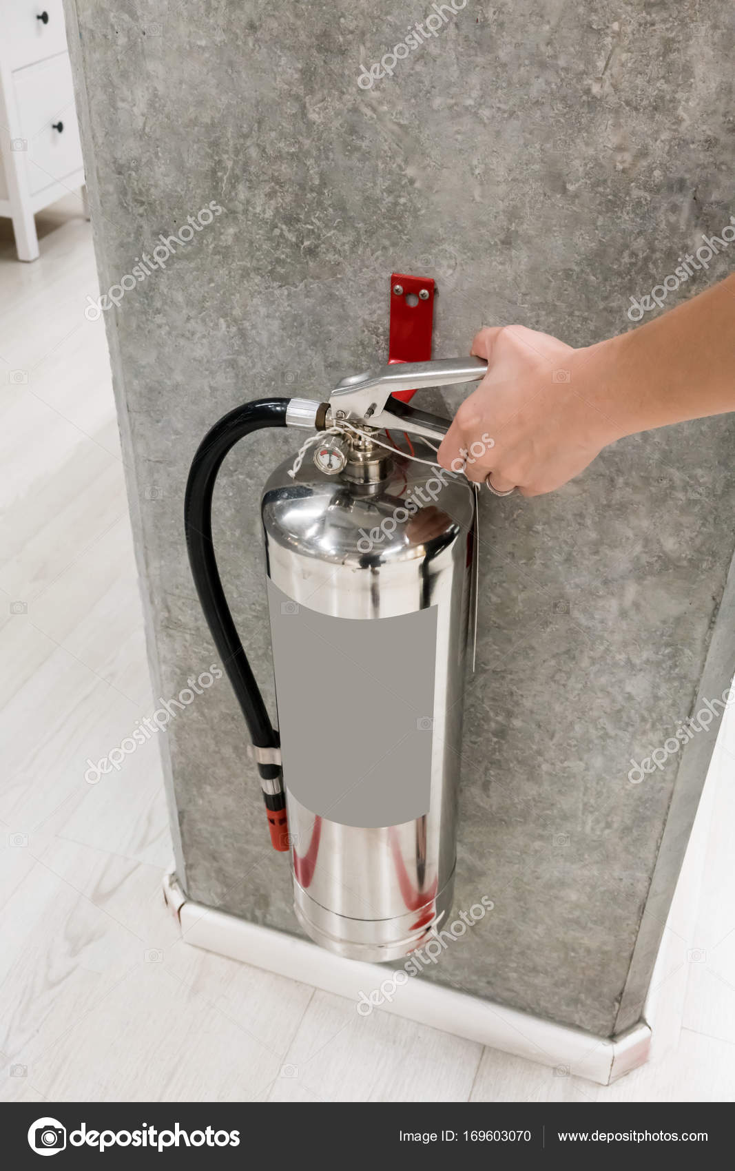 Woman hand touching and checking the chrome fire extinguisher