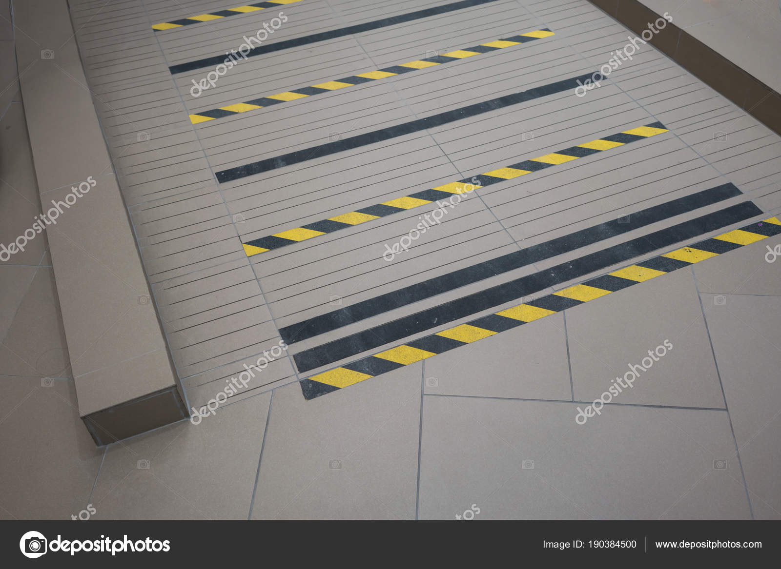 Industrial striped road or step warning on grey ramp for