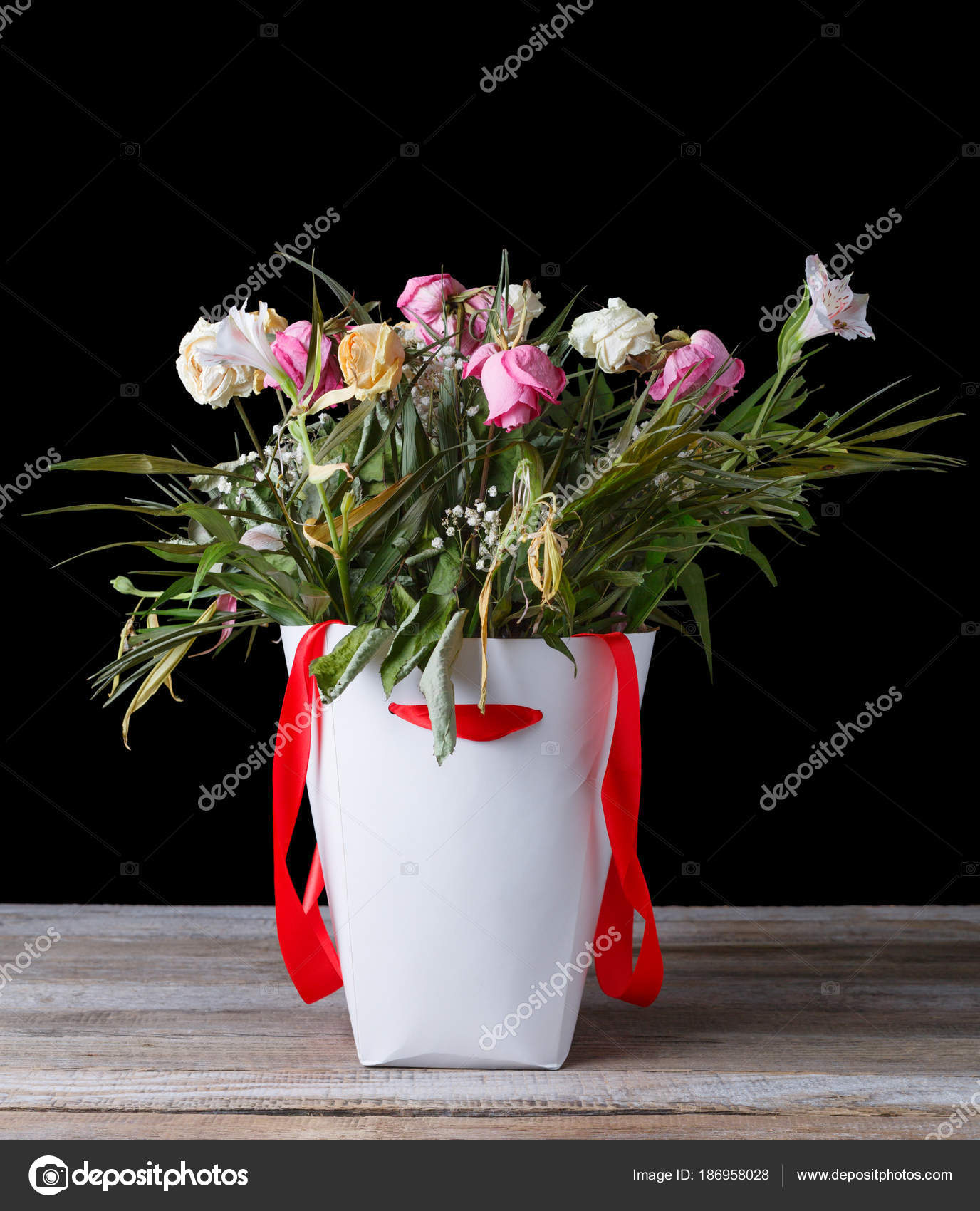 Wilted bouquet of flowers in a white box with a red ribbon on a wilted bouquet of flowers in a white box with a red ribbon on a wooden table izmirmasajfo