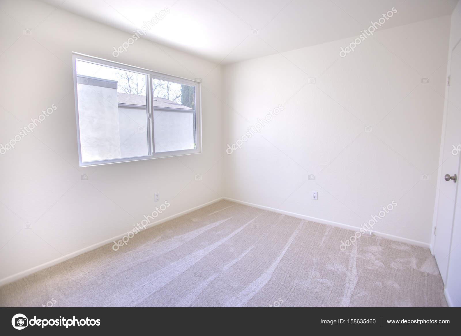 Slaapkamer Met Tapijt : Lege slaapkamer met tapijt en uitzicht buiten venster u stockfoto