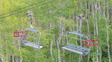 Panorama frame Chairlifts over mountain and trees on a sunny summer day in Park City ski resort