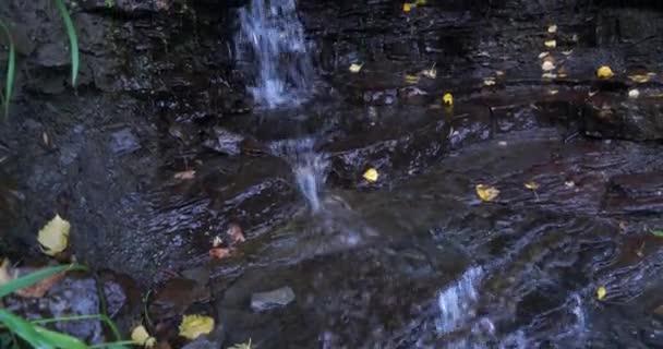 Nahaufnahme, wie Wasser einen Wasserfall im Schatten eines Wanderweges hinunter bewegt wird