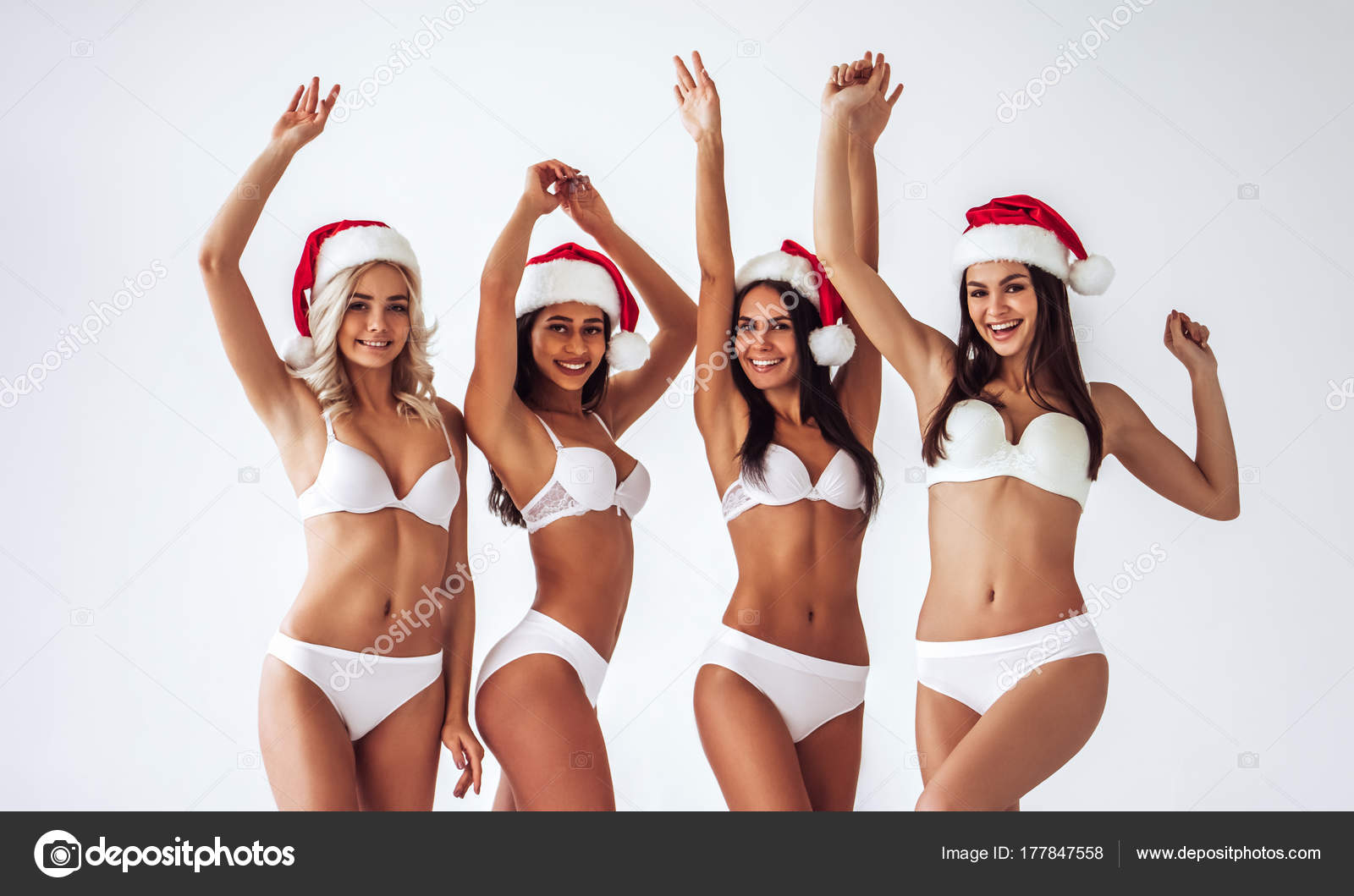 2e1851cc2 Group of young sexy multiracial woman in white lingerie are posing on white  background in Santa Claus hats. Christmas and New Year celebration.