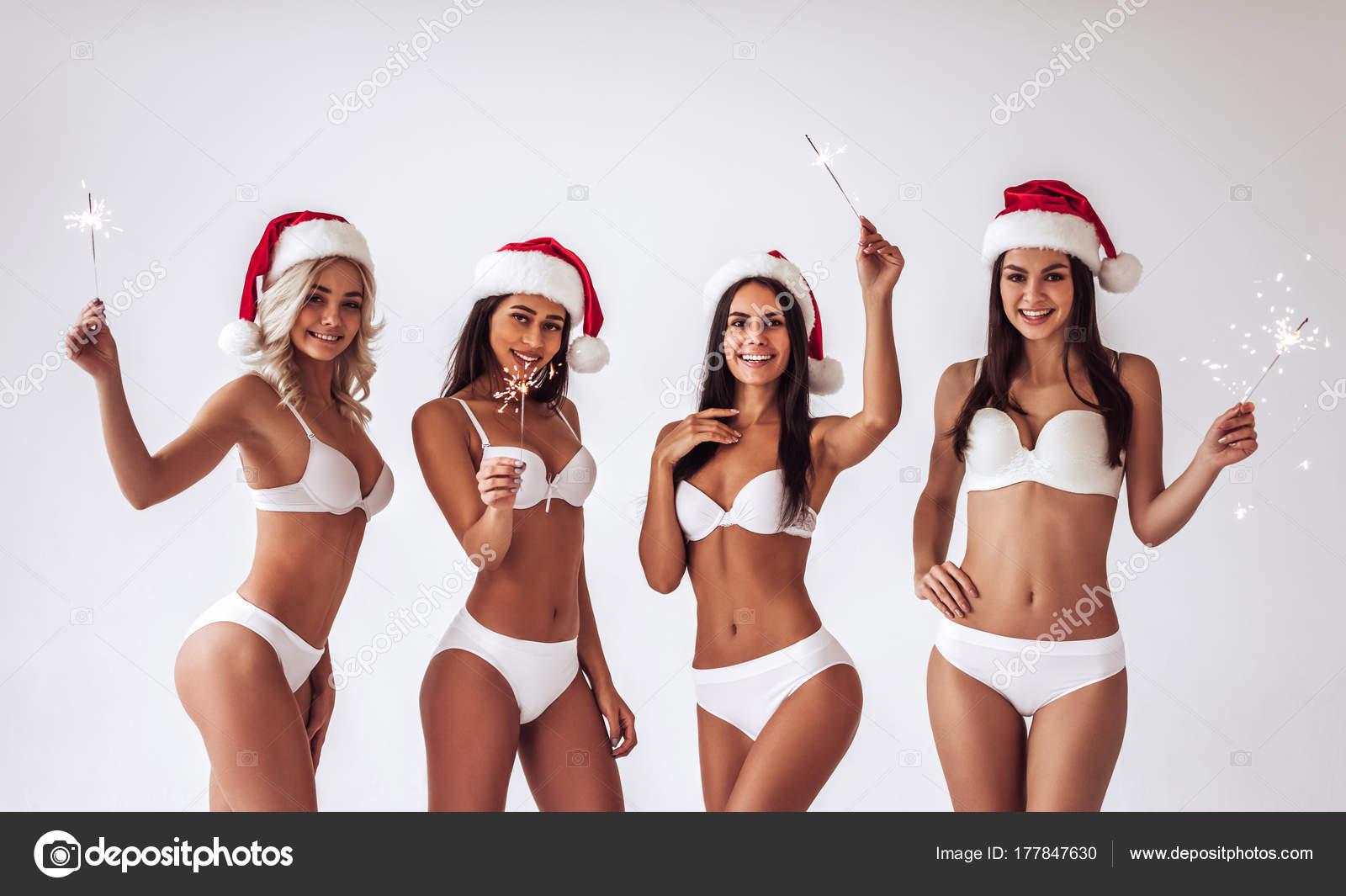 Група молодих сексуальна багаторасові жінка в білому білизна постановки на  білому тлі в Санта-Клауса капелюхи. Новорічні та різдвяні святкування —  Фото від ... e37d53fb3ccbb