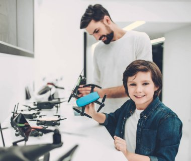 Handsome young man and his cute son are in modern light quadcopter store. Choosing the appropriate drone stock vector