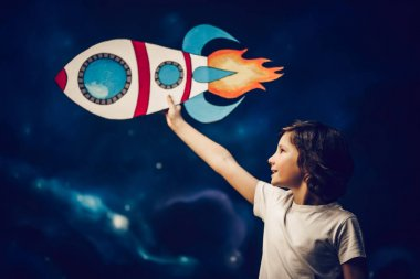 Boy with toy rocket in space