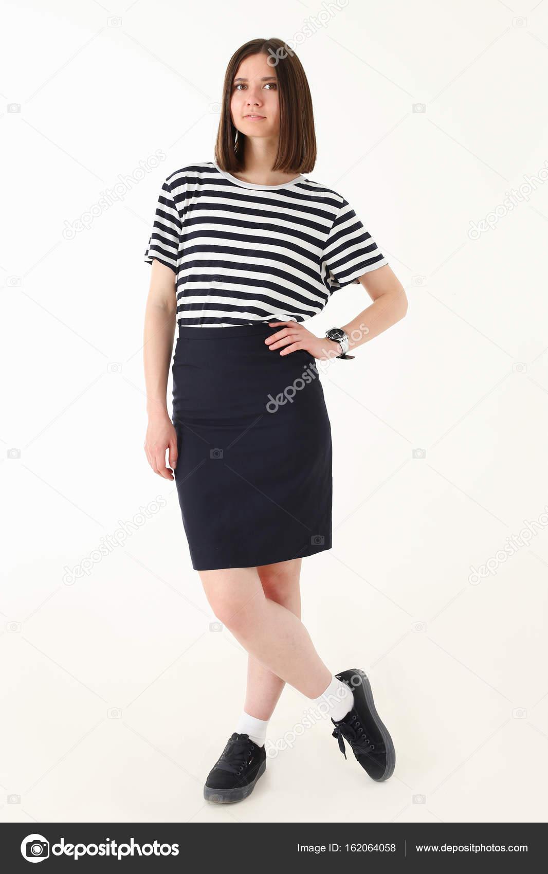 1988689aa2 Modelo de una mujer en una camiseta de rayas y falda sobre un fondo gris en