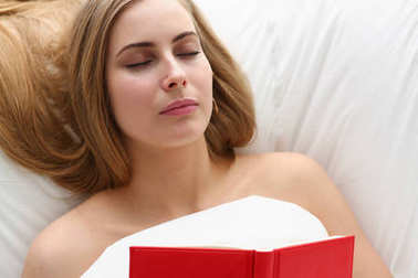 woman fall asleep with book stay in bed
