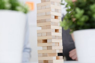 Businessman plays in a strategy of jenga hand