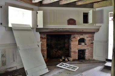 Interior of an old farm house built sometime around the early 1800s. The interior includes a fireplace, old wood beams and a wood floor.