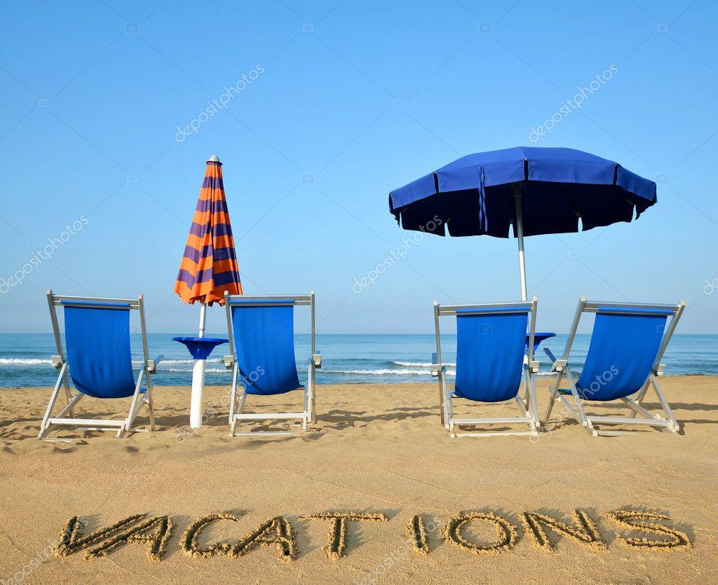 Tumbonas y sombrillas en una playa de arena fotos de for Arena de playa precio