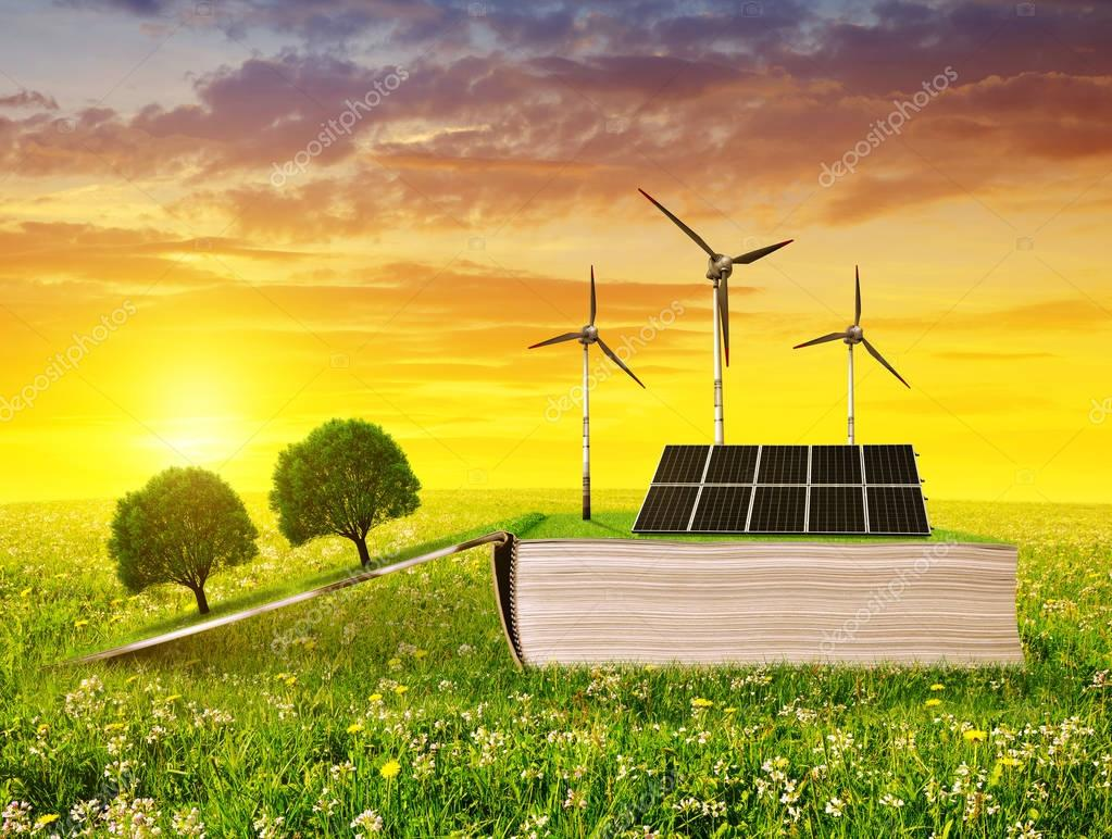 Open ecological book with solar panel and wind turbine on meadow at sunset.