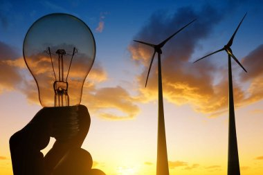 Wind turbines and electrical light bulb in hand.