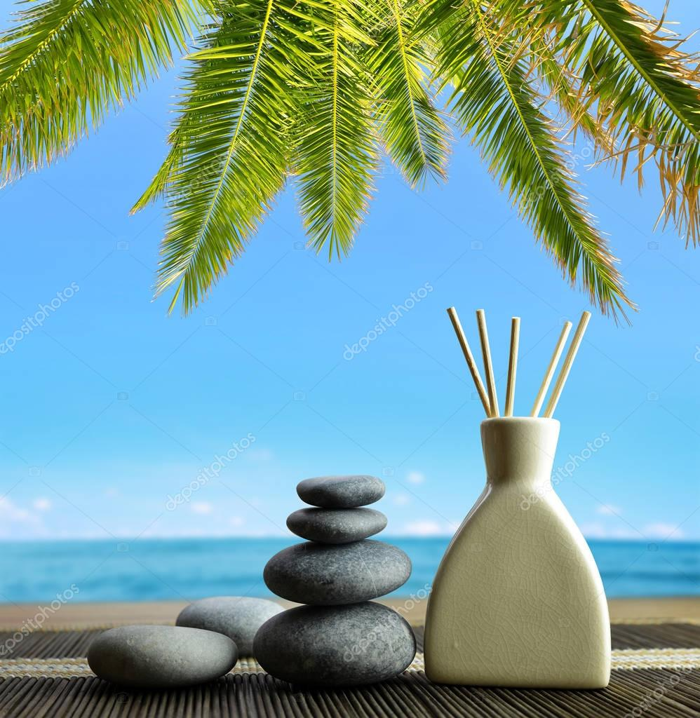 Air freshener with wooden aroma sticks and zen pebbles on the beach. Spa and healthcare concept.
