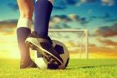 Futball-labda a láb játékos a futballpályán, a naplemente.
