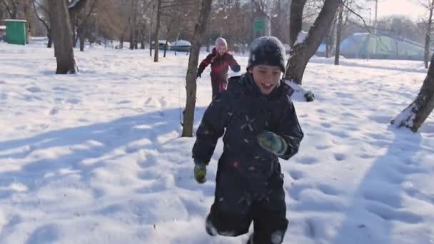Fiatal gyerekek játszani az erdőben a téli naplemente