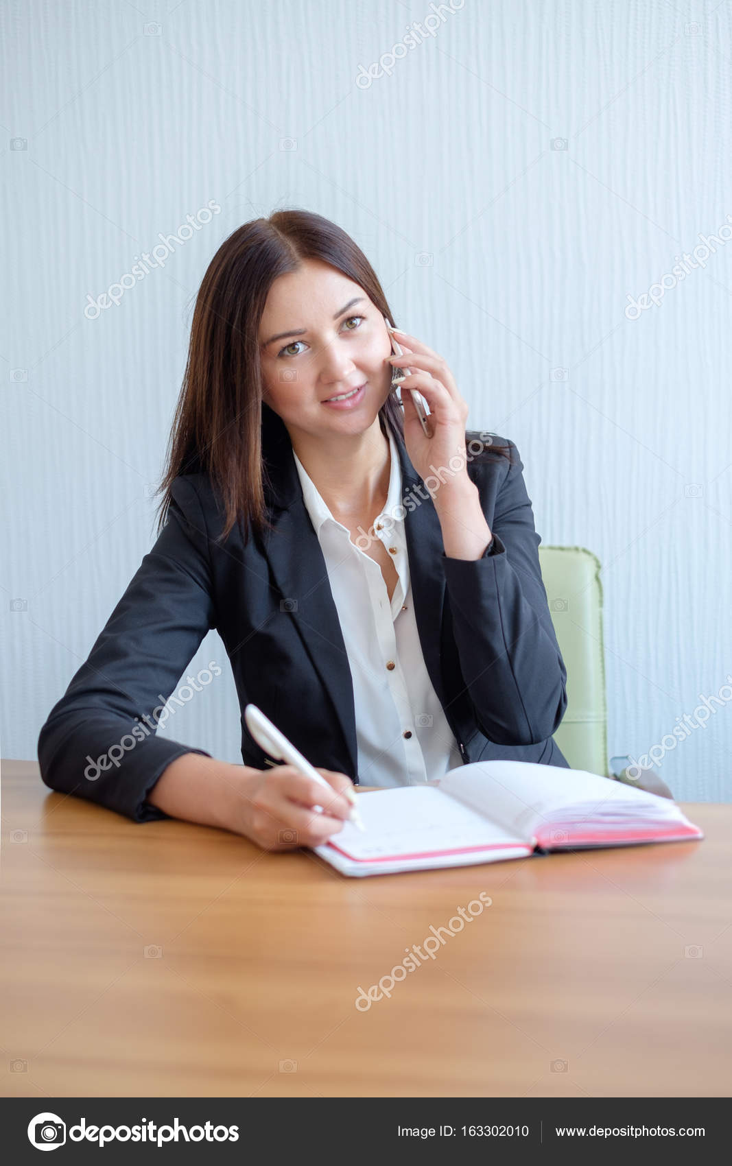 Young Happy Businesswoman Talking On The Phone And Writing