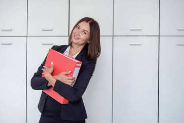 Happy young businesswoman holding a red binder And smiling