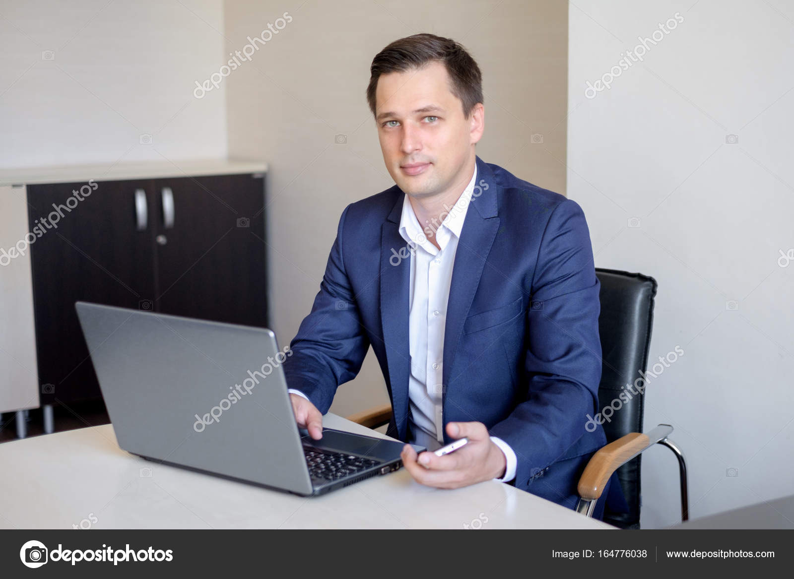 Smiling Young Businessman Sitting Behind His Desk With