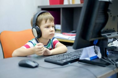 Little boy with headphones sitting at computer in office