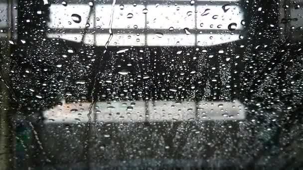 Výhled z vozu na mokré sklo během praní a sušení auto v mytí aut
