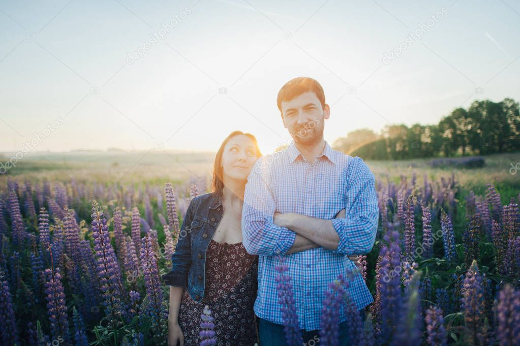 couple in field of flowers in sunset