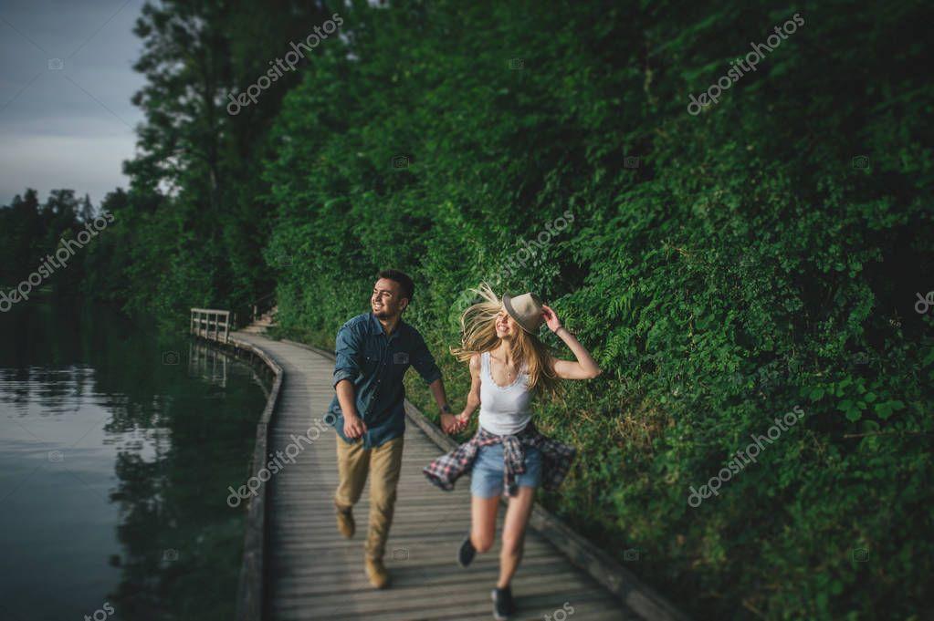 couple running along wooden pier