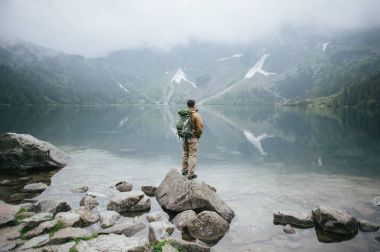 Adventure man hiking wilderness mountain with backpack