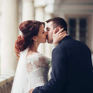 side view of young attractive wedding couple kissing on balcony