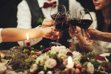 Group of people celebrating wedding and clinking glasses of wine