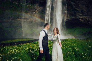 Married couple walking near waterfall