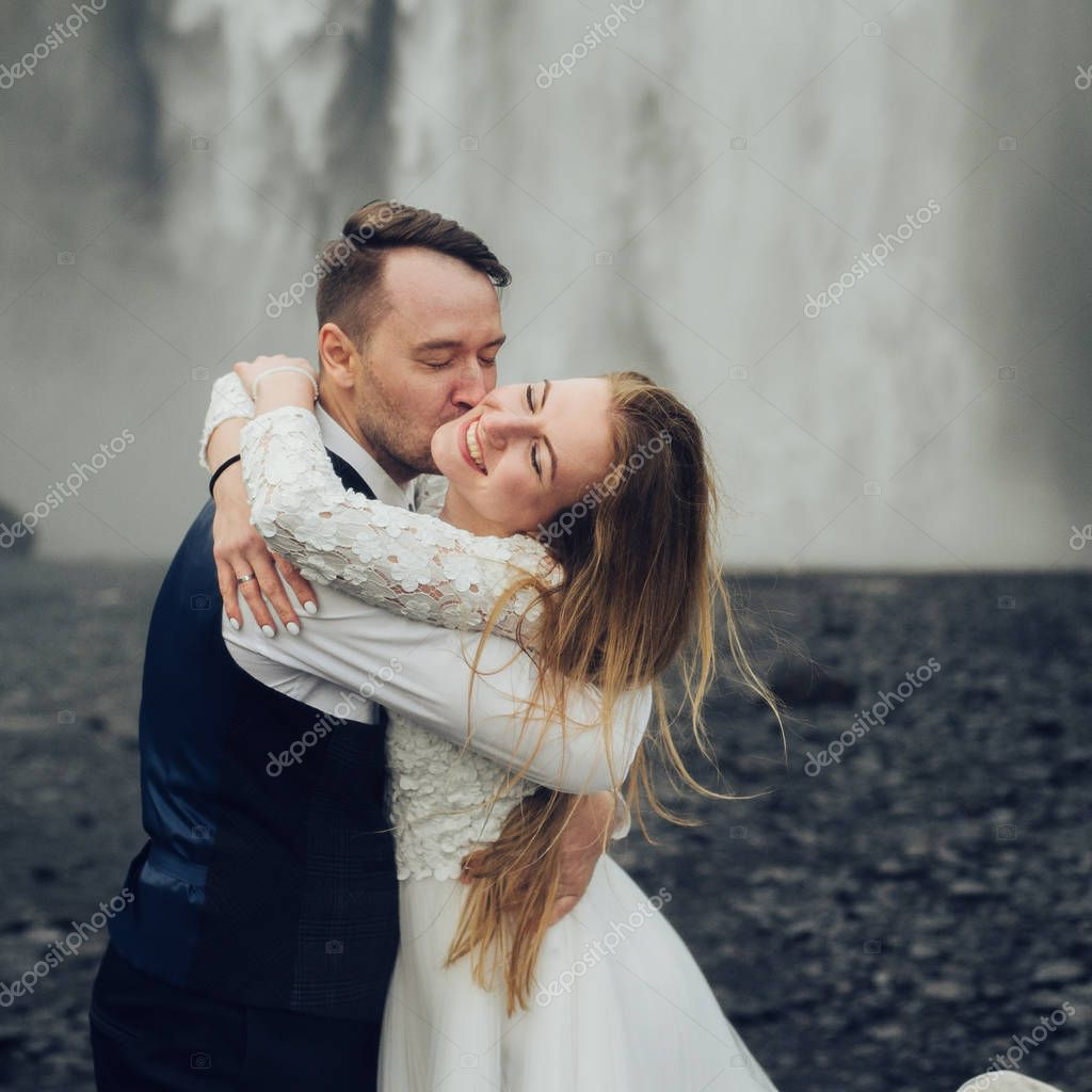 Happy married couple kissing near waterfall at daytime
