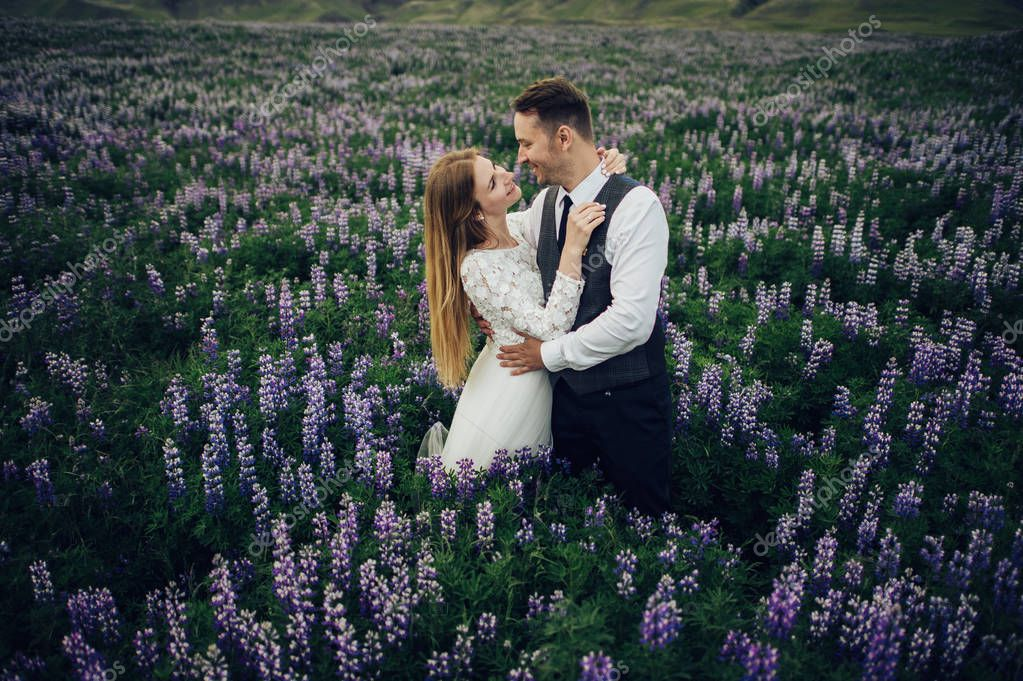married couple posing on field of violet flowers