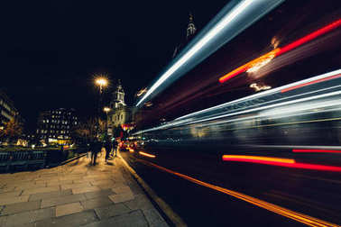 moving red London bus at night