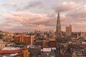 Modern londoni városkép szilánk épület a horizonton, a naplemente, a felhős napon
