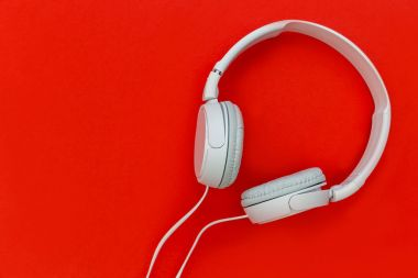 White music headphones on bright red background