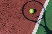 Tenis raketa stín a míč na zelený tenisový kurt