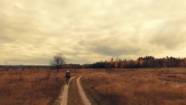 mladý cyklista Cyklistika na prašné cestě pole