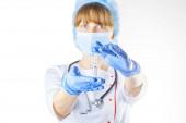 Női orvos fehér kabátban és maszkban, kísérleti gyógyszerrel a kezében. Stúdió fotó