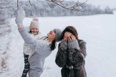 Mother holding smaller daughter in hands and having fun together in winter time