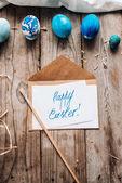 Draufsicht auf Umschlag und Brief mit Frohe Ostern Schriftzug, blauen Eiern, Pinsel, Lappen und Stroh auf Holzbohlen Hintergrund