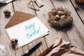 Closeup des Umschlags, Brief mit Frohe Ostern Schriftzug, Stift, Wachteln nisten, Eiern und Threads auf Holzbohlen Hintergrund