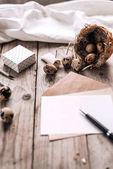 Festliche Komposition mit Wachteleiern im Nest, Geschenkbox, Umschlag mit klarem Brief und Stift, Tuch auf Holzplanken Hintergrund