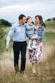 Fotografie Young family hugging and holding daughter in hands while walking on field