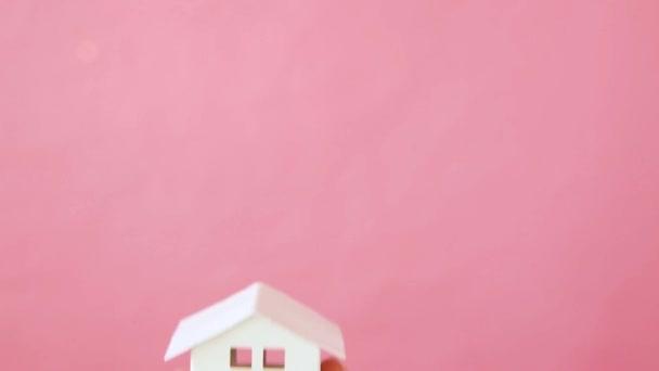 weibliche Hand hält Miniatur-Spielzeughaus isoliert auf rosa Hintergrund