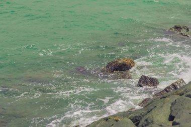 Splashes of waves crashing against the coastal stones.