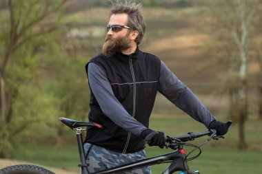 Sports brutal bearded guy on a modern mountain bike. Cyclist on the green hills in the spring.