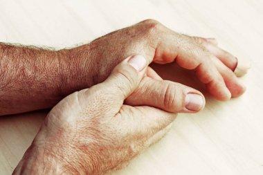 An elderly man has pain in his hands