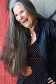 Hlasitě smějící se starší žena s dlouhé šedivé vlasy