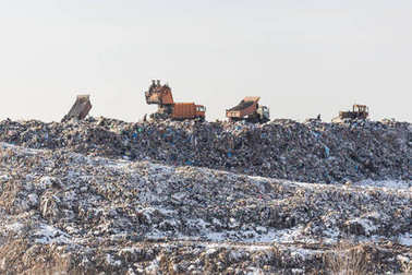 Dump trucks unloading garbage over vast landfill.  Environmental pollution. Outdated method of wasate disposal. Survival of times past
